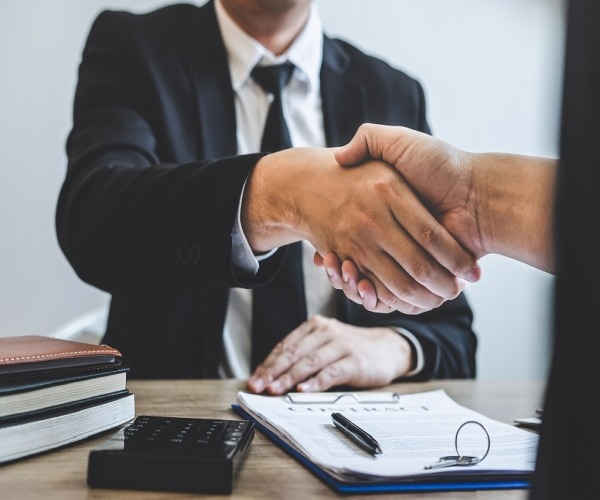 Sales person shaking hands with customer at a desk