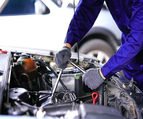 mechanic working on under car bonnet